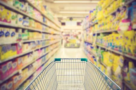 Supermarket interior, empty green shopping cart vintage color
