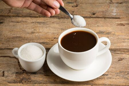 provocative food: Coffee cup detail and teaspoon. Pouring sugar on coffee cup.