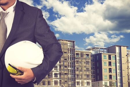 indenture: engineer holding white helmet for workers security on background of new highrise apartment buildings and construction background of blue sky vintage color