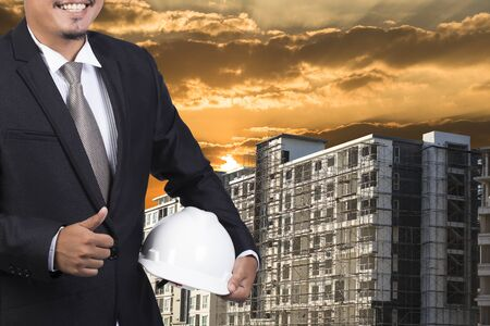indenture: engineer holding white helmet for workers security on background of new highrise apartment buildings and construction background of evening sunset cloudy Stock Photo
