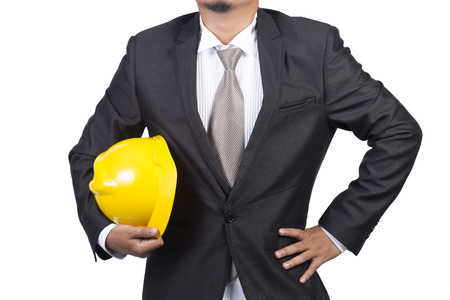 construction management: businessman or engineer holding a helmet under his arm against white background