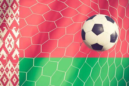 multi national: Belarus flag and soccer ball, football in goal net vintage color Stock Photo