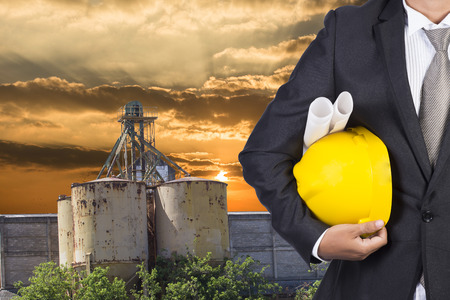 footing: engineer holding helmet for working at footing of building construction site and sunset Stock Photo