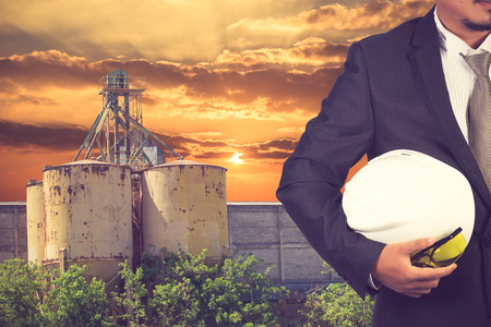footing: engineer holding helmet for working at footing of building construction site and sunset vintage color