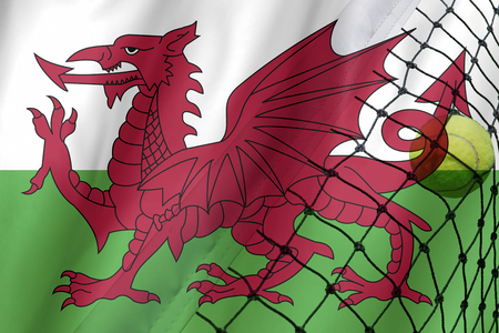 Tennis ball on Wales flag background. Stock Photo