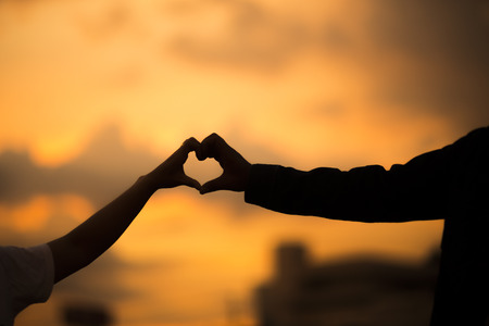 risky love: Happy couple making heart shape and sunset. Love unique concept.