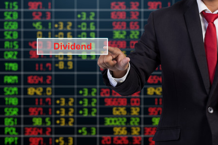 lend a hand: Businessman hand touching Dividend sign on virtual screen