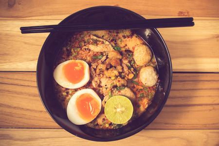 noodles: bowl of noodles with vegetables and soft boiled egg on wooden table. delicious noodle. Instant noodle. hot noodle.Homemade Quick Ramen Noodles with egg.vintage color Stock Photo