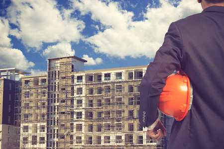 footing: engineer holding helmet for working at footing of building construction site and blue sky vintage color