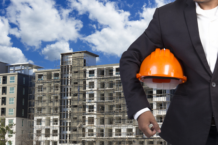 footing: engineer holding helmet for working at footing of building construction site and blue sky