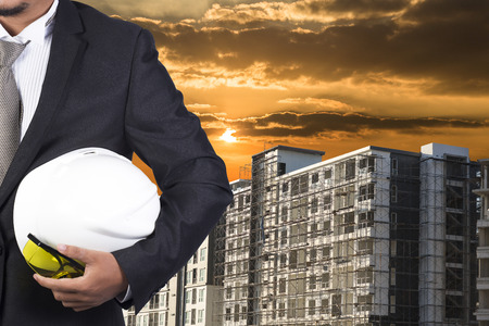 footing: engineer holding helmet for working at footing of building construction site