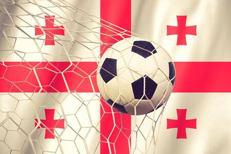 multi national: Georgia flag and soccer ball, football in goal net vintage color Stock Photo