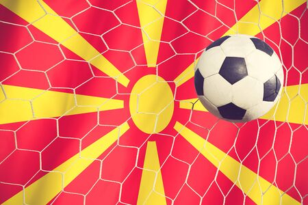 multi national: Macedonia flag and soccer ball, football in goal net vintage color