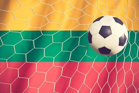multi national: Lithuania flag and soccer ball, football in goal net vintage color Stock Photo