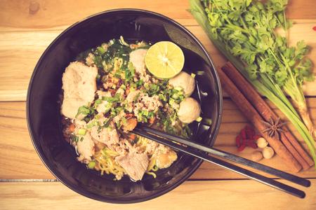 instant ramen: bowl of noodles with vegetables on wooden table. delicious noodle. Instant noodle. hot noodle.Homemade Quick Ramen Noodles vintage color Editorial