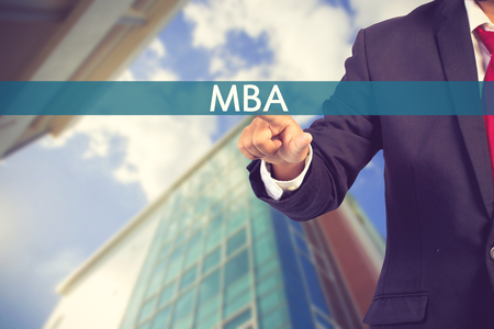 administracion empresarial: Businessman hand touching MBA (or Master of Business Administration) sign on virtual screen vintage color