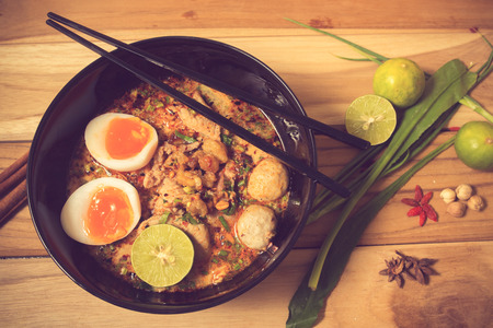 instant ramen: bowl of noodles with vegetables and soft boiled egg on wooden table. delicious noodle. Instant noodle. hot noodle.Homemade Quick Ramen Noodles with egg.vintage color Stock Photo