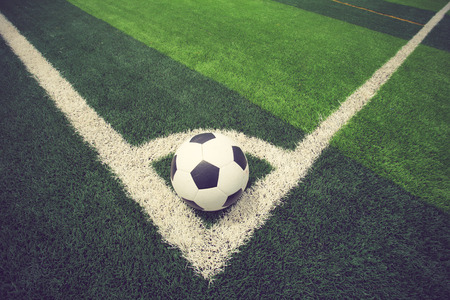 ballsport: soccer ball or football on soccer field vintage color Stock Photo