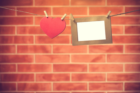 clothesline: Blank photos hanging on a clothesline over brick wall background with copy space.vintage color