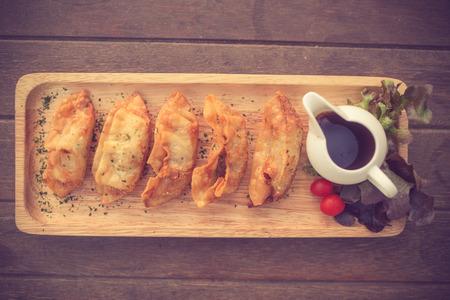 tetsubin: Traditional asian pan fried gyoza dumplings with a dip sauce.Vintage color