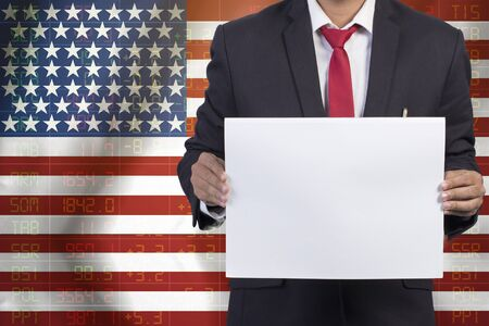 sell shares: businessman in black suit holding sign empty on Flag of USA Business Concept