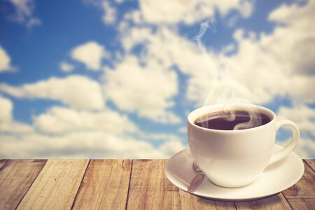 puffy: Morning coffee cup with beautiful blue sky and puffy clouds background.Vintage Color Stock Photo