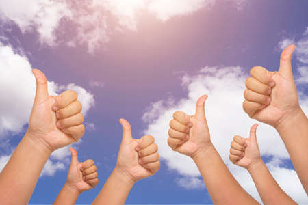 congratulate: Many people congratulate a winner and holding their thumbs up on blue sky background