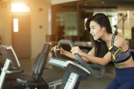 Happy woman riding an exercise bike in gym