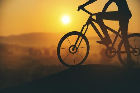 siluetas: Silhouette of a woman on muontain bike, sunset.Vintage color Stock Photo