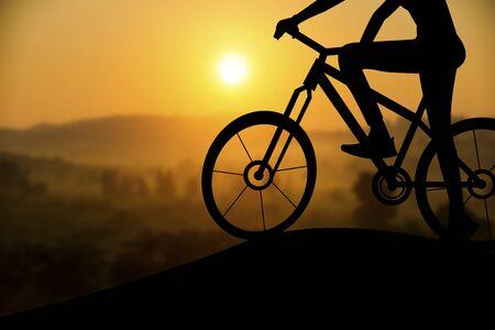 siluetas: Silhouette of a man on muontain bike, sunset