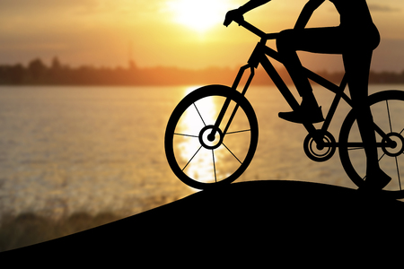 Silhouette of a woman on muontain bike, sunset. Stock Photo