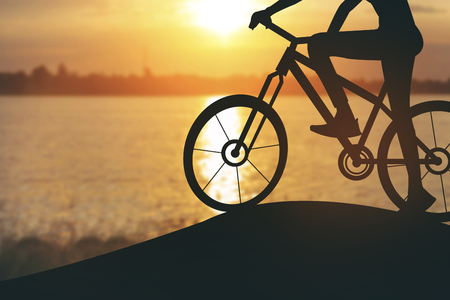 Silhouette of a woman on muontain bike, sunset.Vintage color Stock Photo