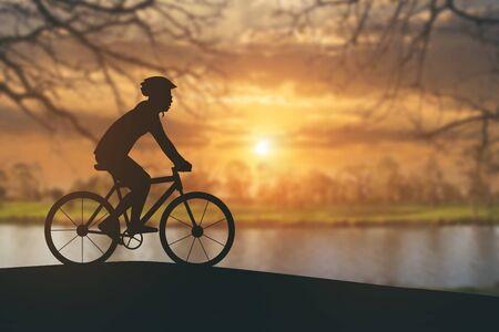 siluetas: Silhouette of a man on muontain bike on public park at sunset.