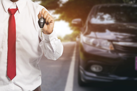 key handover: Male holding car keys with car on background