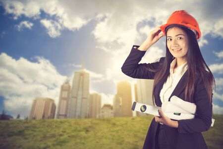 professional asian business woman supervising construction site with hard hat protection at work.Vintage color Reklamní fotografie