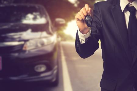 businessman showing a car key - car sale & rental business concept.Vintage color Stock Photo
