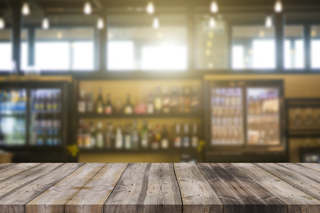 Wood bar top on blur colorful alcohol drink bottle background