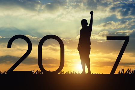 Silhouette young man jumping on the sunset and 2017 years while celebrating new year Standard-Bild