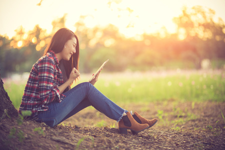 Euphoric woman searching job with a laptop in an urban park in summer.Vintage color Stock Photo
