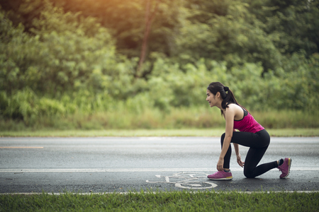 young woman runner tying shoelace on country road Reklamní fotografie