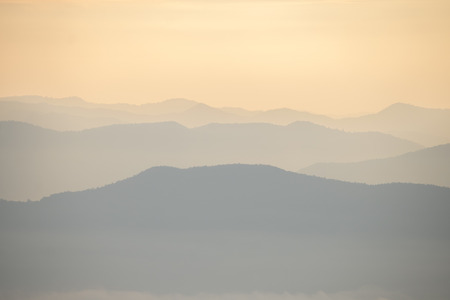 Layer of mountains and mist during sunset
