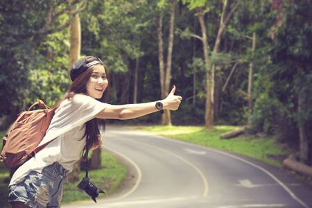 Young beautiful woman hitchhiking standing on road. Standard-Bild