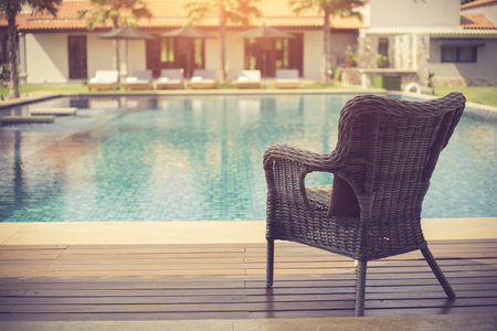 Relaxing rattan chairs beside swimming pool