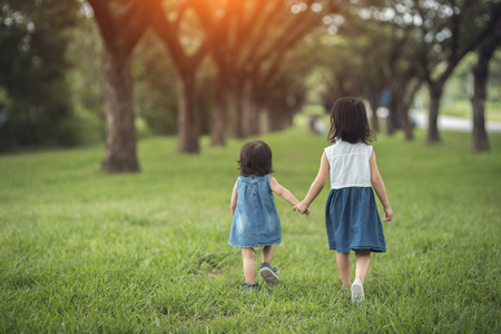 Two little sisters holding each other hands and running forward.Vintage color Reklamní fotografie - 108662965