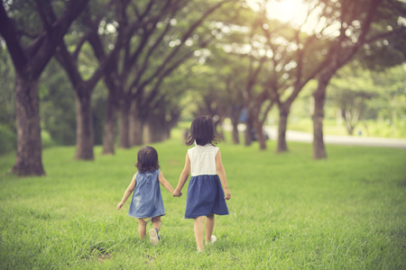 Two little sisters holding each other hands and running forward.Vintage color