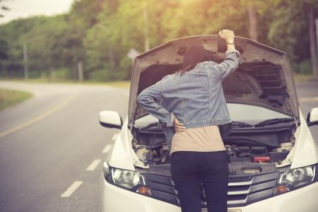 Vrouwenspectie Ze opende de motorkap Kapotte auto aan de zijkant Zie motoren die beschadigd zijn of niet. Vintage kleur Stockfoto
