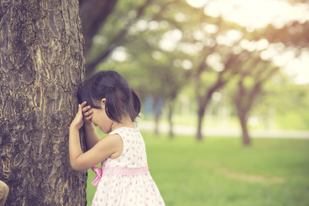 little girl is playing hide-and-seek hiding face in the park.Vintage color