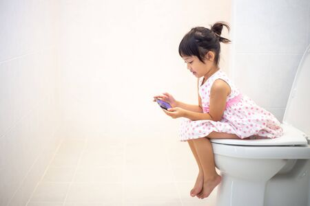 asian children sitting on a toilet and holding smartphone.
