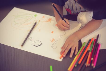 Kids drawing on floor on paper.vintage color Banco de Imagens