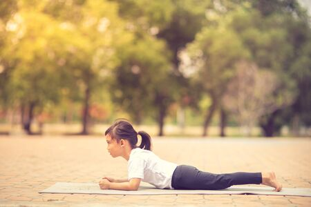 Little cute asian girl practicing yoga pose on a mat in park, Healthy and exercise concept Reklamní fotografie
